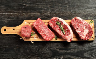 Fresh raw Prime Black Angus beef steaks on wooden board: Tenderloin, Denver Cut, Striploin, Rib Eye