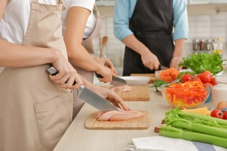 Woman cutting chicken fillet at cooking classes